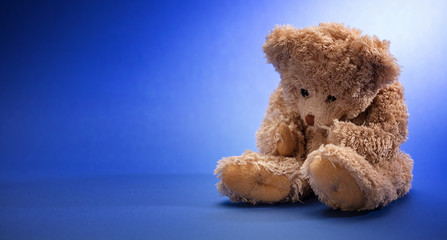 Teddy bear sad, holding his head, sitting in blue empty room background, copy space