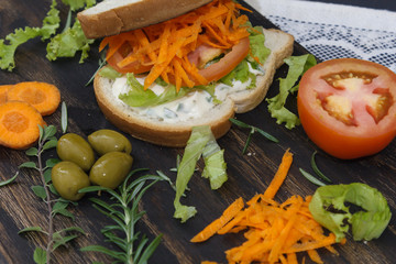Healthy vegetarian sandwich with carrot, Tomato, lettuce and spices, served on an wooden board.