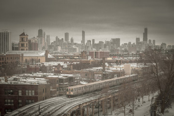 Moody Chicago skyline with snow and train on cold day
