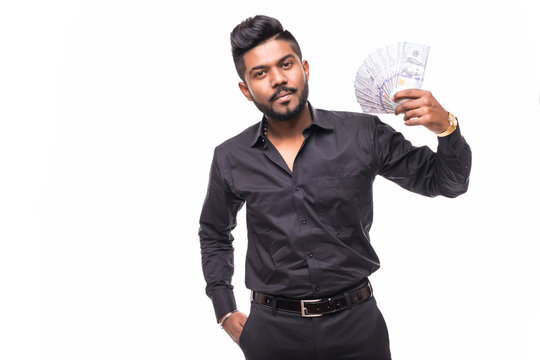 Portrait of bearded hipster young man holding money dollar bills in hand, isolated on white background.
