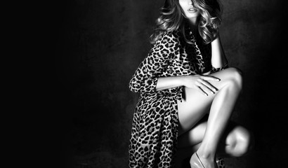 Beautiful sexy woman posing in Leopard trendy dress on dark  background. Black and white