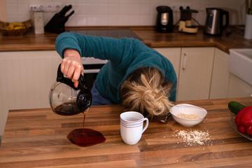 Müde Frau mit Kopf auf Tisch verschüttet ihren Kaffee