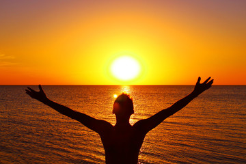 A young man with his arms outstretched is watching the sunset on the seashore. Background. Landscape.