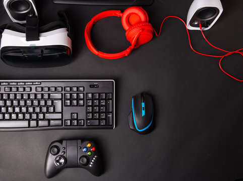 Top view a gaming gear, mouse, keyboard, joystick, headset, VR Headset on black table background.