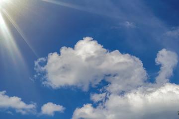 Beautiful blue bright sky, white cumulus clouds and sun rays