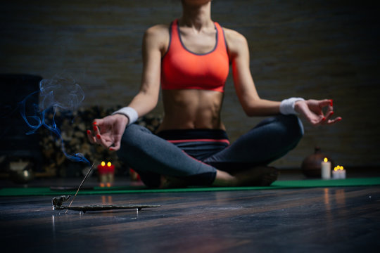 Selective focus of incense stick and woman meditating