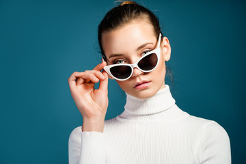 Portrait of a beautiful young girl in white knitted golf and sunglasses on a blue background