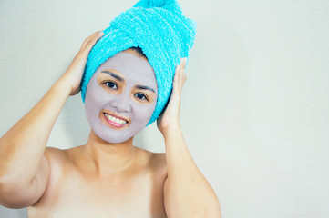 Happy woman with a clay mask. Photo of attractive young woman with towel on her head on beige background.