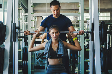 Personal fitness trainer assisting a young woman.