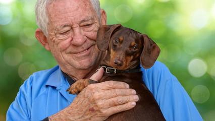 Senior man holding his beloved puppy