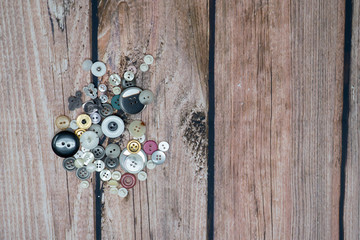 Pile of random colorful shiny sewing buttons isolated on a wood background