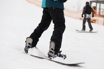 Snowboarder on slope at resort, closeup. Winter vacation
