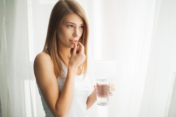 Happy smiling positive woman eating the pill and holding the glass of water in the hand, in her home
