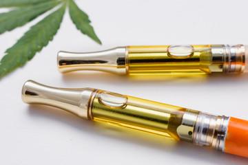 Full Gram THC/CBD Concentrated Oil In Cartridges Closeup Marijuana Leaf On White