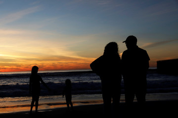 People are seen in silhouette along the U.S. and Mexico border fence at Friendship Park in Tijuana