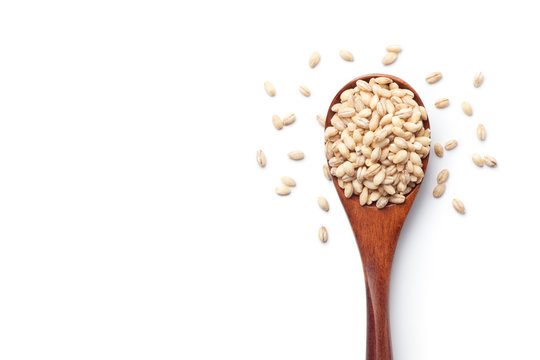 Peeled barley in a wooden spoon, isolated on white background. Top view.
