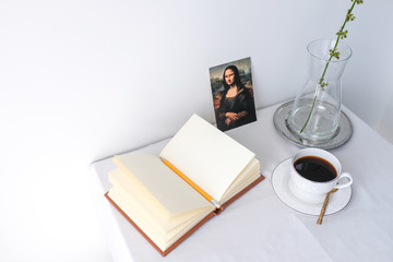 Glass vase of dried flower plant a white vintage ceramic cup of coffee blank open notebook and mona lisa on white table top on white wall background with blank copy space for product mock up placement