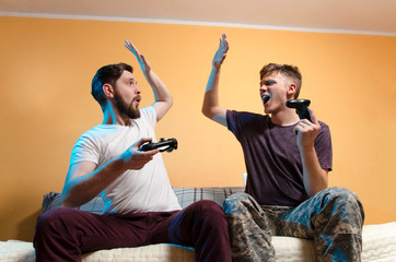 Young adult man and teenager giving high five to each other while playing video games