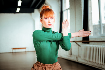 Pleasant-looking red haired girl in a turtleneck stretching her arms