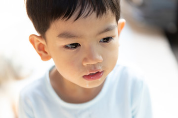 Close up mucus flowing from nose, Asian boy has a runny nose with clear snot.