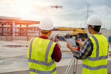 Drone operated by construction worker on building site,flying with drone. Wall mural