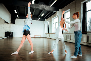 Professional modern dance teacher with red hair showing movements
