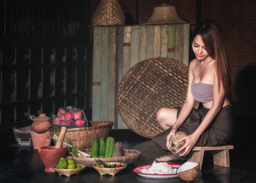Sexy woman sit on coconut grater and grate coconut into bowl.