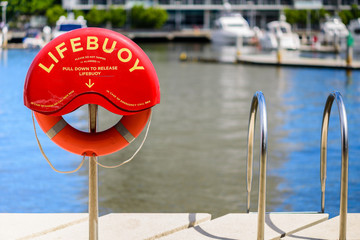 A lifebuoy on a post next to a stainless steel fence on the bank of the Yarra River in Docklands, Melbourne, Victoria, Australia