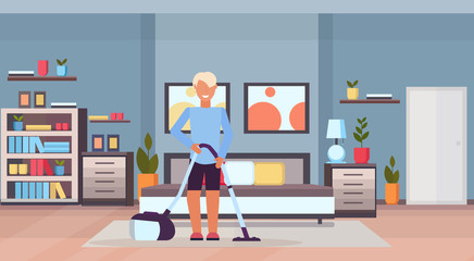 man cleaning bedroom floor with vacuum cleaner guy using vac modern home apartment living room interior flat full length horizontal