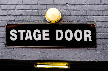 A 'Stage Door' sign with white on black lettering, on a brick wall and a lamp above