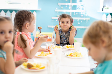 Group of children eating healthy foo in kindergarten