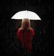 The girl stands with her back with a white stylish umbrella in the rain on a black background. Stylish and fashionable photography.