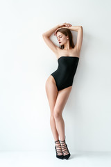 Full length fachion portrait of sexy woman posing in black swimsuit
