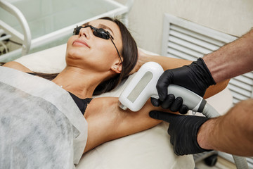 Beautician applying hair removal or laser epilation in armpit zone