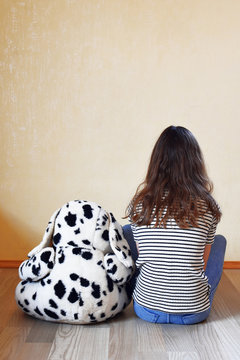 Lonely teenage girl wearing striped t-shirt and plush toy dog sitting on floor and looking at light yellow wall at empty room back view indoors. Autism and children care and protection concept.