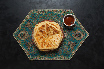 Arabic Cheese Bread with red sauce on a black table.