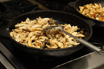 Beef meat with mushrooms fried in a pan, close-up, background, slow motion, kitchen