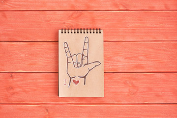 Notebook of Kraft paper with a painted symbol ASL (American Sign Language) ILY (I Love you) that lies on the textured wooden plank of the color Living Coral, flat lay, top view, copy space