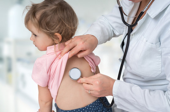 Pediatrician doctor examining a little girl by stethoscope