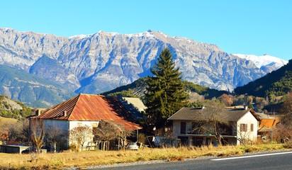 A small village near the road in french Alps near lac de serre-poncon on a sunny day. Ecrins massif