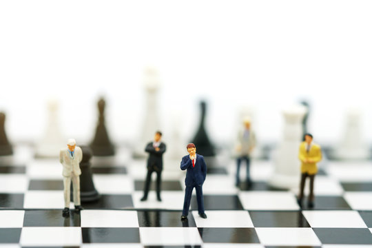 Miniature people: Businessman handshake to business success on chessboard. Commitment, agreement, investment and partnership concept