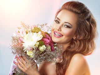 Happy beautiful girl with flowers in hands