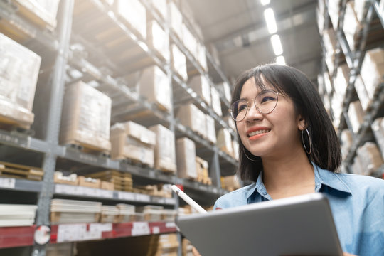 Close up of young attractive asian woman, auditor or trainee staff work stocktaking inventory in warehouse store by computer tablet with wide angle view. Asian entrepreneur or small business concept.