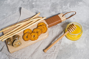 set of crackers on wooden cutting Board, honey, grey background