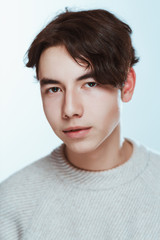 Studio portrait young man in grey sweater on white background