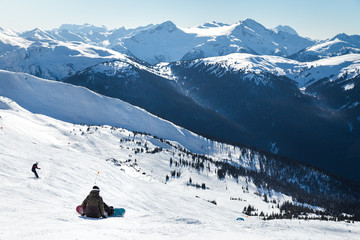 Snowboarder on a hill at the top of Blackcomb, 7th Heaven, with a view looking toward Whistler on a sunny day.