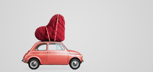 Living coral retro toy car delivering craft heart for Valentine's day on gray background