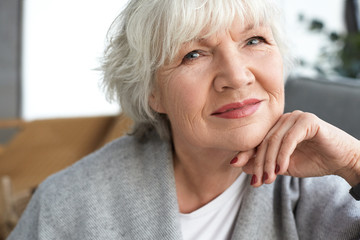 Close up image of adorable charming female pensioner with white short hair, wrinkles and wise blue eyes relaxing at home, having happy look, looking at camera. Beauty, style and maturity concept