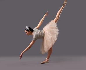 Ballerina bending down and raising one leg up in studio