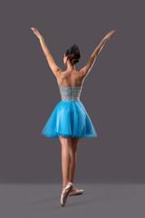 Ballerina raising hands up on grey isolated background